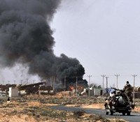 Smoke billows as Libyan rebels progress westward from the town of Bin Jawad towards Muammar Gaddafi's home town of Sirte yesterday as NATO finally agreed to take over full command of military operations to enforce a no-fly zone in Libya from US-led coalition. — AFP.