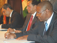 Essar Holdings' Middle East and Africa resident director Mr Firdhose Coovadia (left) and Industry and Commerce Minister Welshman Ncube sign the contract for the disposal of Ziscosteel to the Mauritian firm while, Essar's Group vice chairman Mr Ravi Ruia (centre) looks on.