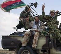 Libyan rebels head towards an area where they are engaged in street battles with forces loyal to Muammar Gaddafi near Brega yesterday.