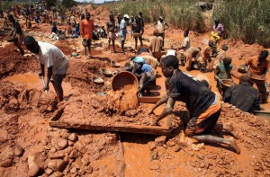 Muddied prospectors pan for gold in Manica Province