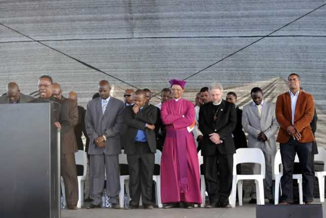 SOUTH AFRICA — Religious leaders attend a memorial service yesterday in Marikana to commemorate the Marikana massacre. Today marks a year after police opened fire on thousands of strikers at platinum producer Lonmin's mine northwest of Johannesburg which killed 34 and injured 78 people. The August shooting was described as the worst police brutality since the end of apartheid two decades ago. Three days before the commemoration the firm has recognised radical labour group AMCU, which led the wage strike, in an attempt to ease simmering inter-union tensions on the platinum belt.— AFP.