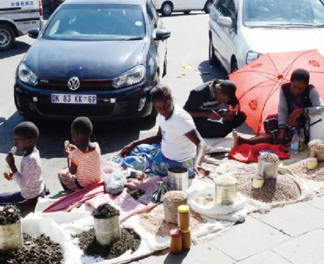 Vendors ply their trade on a pavement in this file photo