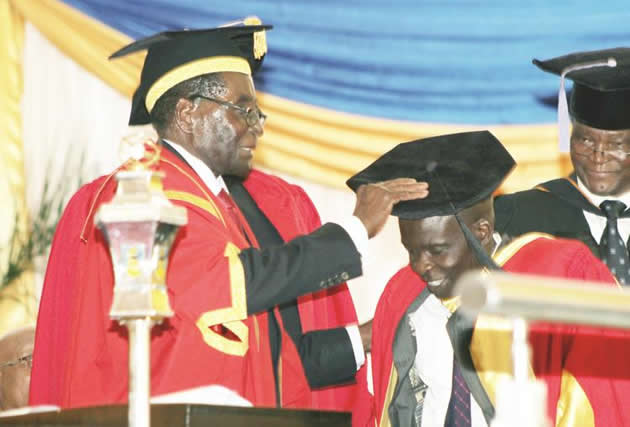 Nust Chancellor President Mugabe confers a Doctor of Philosophy Honoris Causa on Obadiah Moyo who is a librarian and founder of Rural Libraries and Resources Development during a graduation ceremony at the institution in Bulawayo. (Picture by Eliah Saushoma)