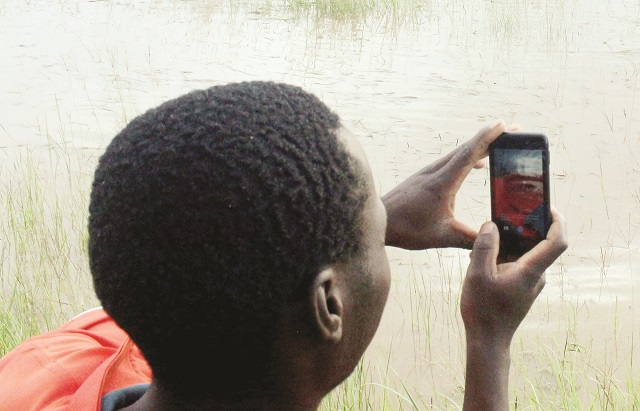 Some villagers and farmers' crops in Umguza District, Matabeleland North Province, were seriously affected by Cyclone Dineo-induced floods as their maize crop which was at tasseling stage was submerged in water. The picture taken last year at Mtambo Village shows a passerby taking a picture of the submerged crop. — Picture by Eliah Saushoma