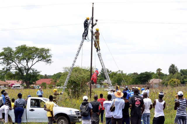 Rescue workers lower the body of a suspected cable thief from a power line in Queens Park, Bulawayo yesterday