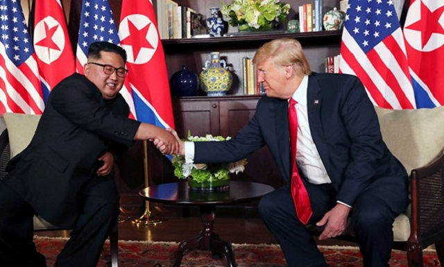 US President Donald Trump and North Korea's leader Kim Jong Un shake hands after signing documents during a summit at the Capella Hotel on the resort island of Sentosa, Singapore yesterday